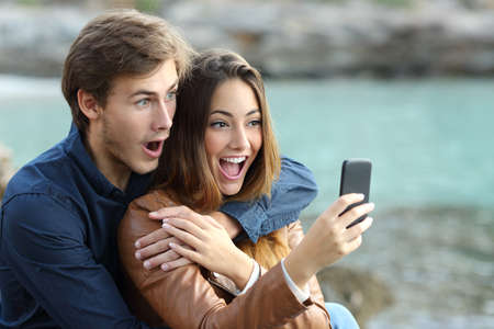 lady: Shocked couple watching a smart phone on holidays on the beach