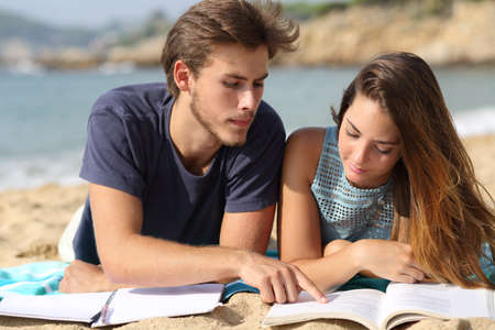 serious: Teenager couple or friends students studying on the beach learning together