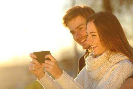to phone: Happy couple watching media videos in a smart phone at sunset on the beach