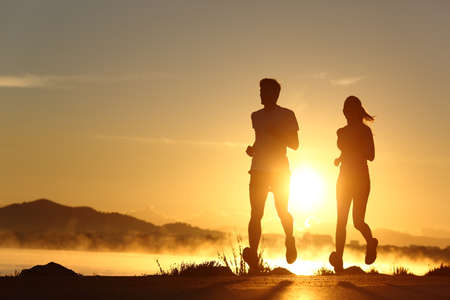Silhouette of a couple running at sunset with the sun in the background Stock Photo