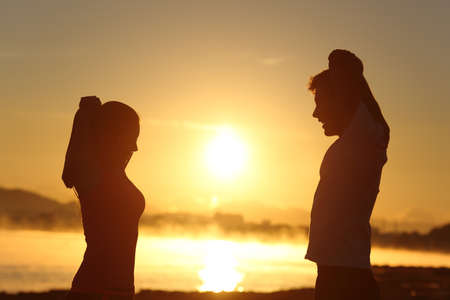 life partner: Silhouette of a fitness couple stretching at sunrise with the sun in the background Stock Photo
