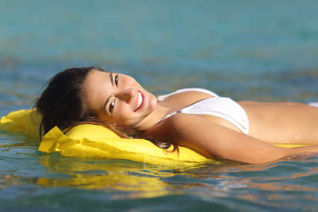 Tourist woman bathing in a tropical sea floating on an inflatable bed and enjoying summer holidays