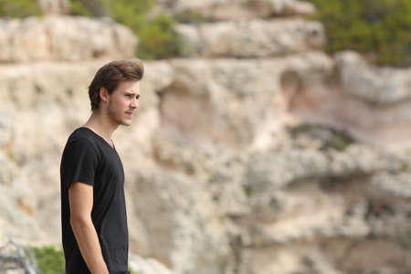 Portrait of a man exploring and looking away in the mountain with an unfocused background photo