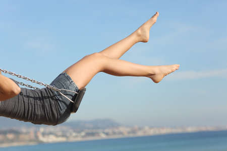 Hair removed woman legs swinging on the beach with the sky in the background
