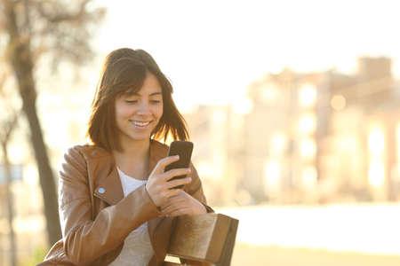 adolescente: Muchacha feliz que usa un tel�fono inteligente en un parque de la ciudad que se sienta en un banco Foto de archivo
