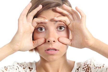 insomnio: Mujer cansada abriendo los ojos con los dedos aislados en un fondo blanco Foto de archivo
