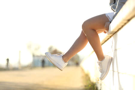 modern girls: Urban teenager legs silhouette wearing sneakers sitting on a wall