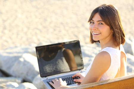 fiestas electronicas: Mujer feliz escribiendo en un ordenador portátil y mirando la cámara sentado en un banco