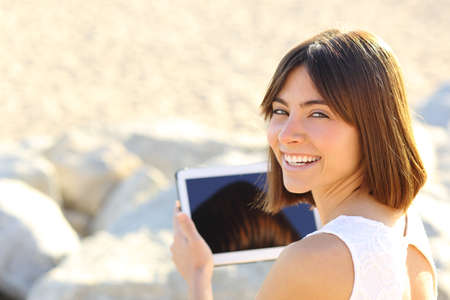 Happy woman using a tablet and looking at camera outdoors photo