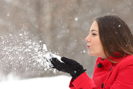 profile face: Side view of a candid woman in red blowing snow in winter during a snowfall
