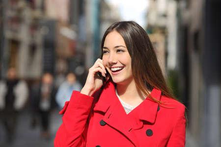 llamando: Mujer alegre que habla en el teléfono en la calle con una chaqueta roja