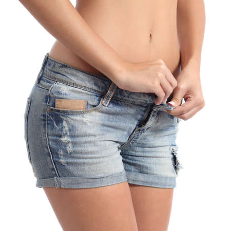 Closeup of a fitness woman buttoning her shorts diet concept isolated on a white background photo