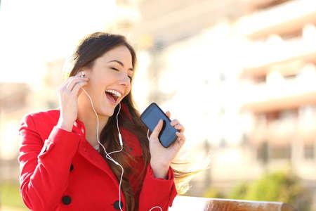 persona cantando: Funny girl escuchar la m�sica con los auriculares de un tel�fono inteligente con un fondo fuera de foco urbano Foto de archivo