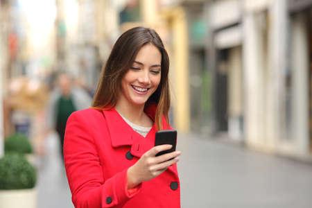 Meisje wandelen en SMS op de slimme telefoon in de straat dragen van een rode jas in de winter