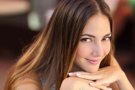 yeux: Portrait d'une femme confiante avec la peau lisse regardant la cam�ra avec un arri�re-plan flou
