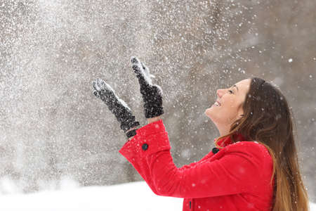 and in winter: Woman wearing a red jacket throwing snow in the air in winter holidays