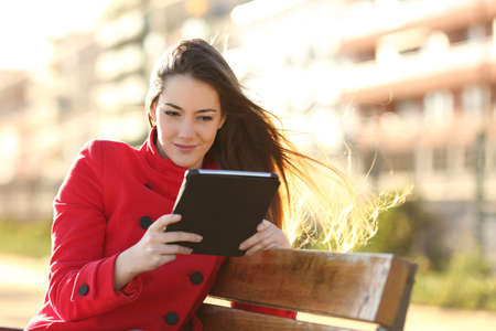 aprendizaje: Mujer leyendo un libro electrónico o tableta en un parque urbano con edificios en el fondo