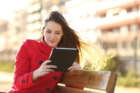 Vrouw het lezen van een ebook of tablet in een stedelijk park met gebouwen op de achtergrond