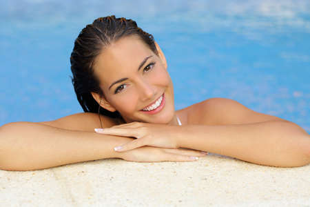 orthodontie: femme de beauté avec la peau parfaite et dents blanches dans un côté de la piscine en regardant la caméra Banque d'images