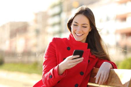 Fille SMS sur le téléphone intelligent assis dans un parc vêtu d'une veste rouge et assis dans un banc dans un parc Banque d'images - 37189365