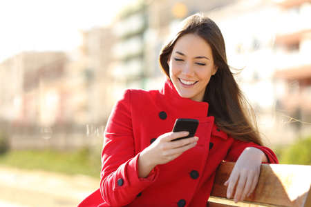 Girl texting on the smart phone sitting in a park wearing a red jacket and sitting in a bench in a park Standard-Bild