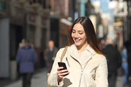 winter people: Happy girl walking and texting on the smart phone in the street in winter wearing a white jacket