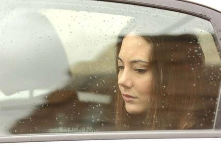Sad woman looking down through a car window in a rainy day