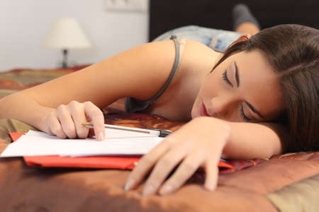 Student tired and sleeping in her bed room over the notes while was studying Stock Photo