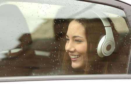 Happy teenager with headphones listening to the music inside a car and looking away