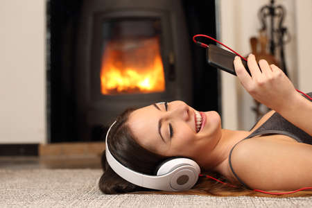 listening to people: Woman listening to the music from a smartphone lying on the floor at home with a fireplace in the background Stock Photo