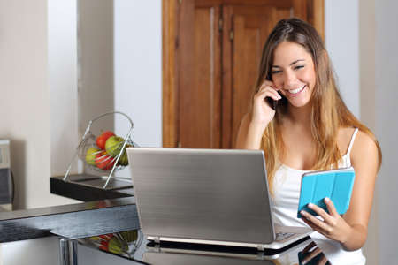 Entrepreneur woman multi tasking working with a laptop tablet and phone in the kitchen at home Stockfoto