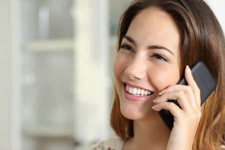 自宅で携帯電話で話している幸せな女の肖像画間近します。