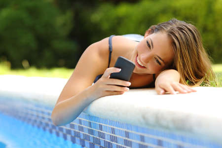 Happy woman using a smart phone in a poolside of her garden pool in summer