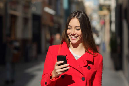 looking towards camera: Happy woman using a smart phone while is walking in the street in a sunny day