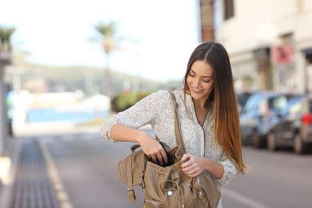 Mujer feliz ocasional que recorre en la calle y buscar algo en una bolsa
