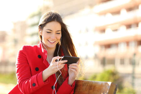 earbud: Woman watching videos in a smart phone with earphones sitting in a park with an unfocused buildings in the background