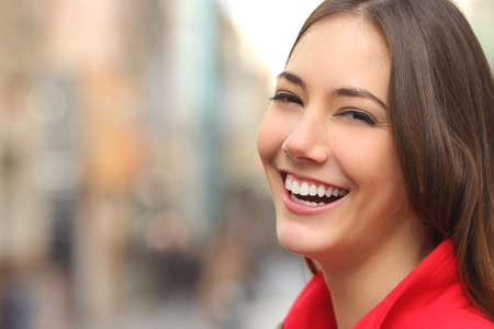 makeup model: Donna bianca sorriso con denti perfetti in strada e guardando la fotocamera