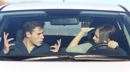 car front: Couple arguing while she is driving a car in a dangerous situation Stock Photo