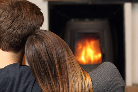 fire place: Comfortable couple hugging at home resting near fire place