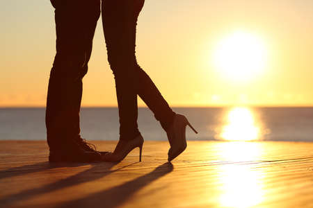 a pair of: Couple legs silhouette falling in love hugging at sunset on the beach with the sun in the background