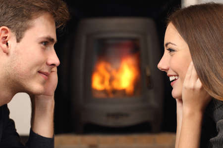 front side: Side view of a couple flirting and looking each other in front a fireplace