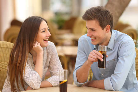 sight: Happy couple or friends talking in a restaurant and looking each other