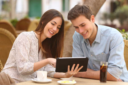 urban planning: Happy couple watching media in a tablet in a restaurant terrace Stock Photo