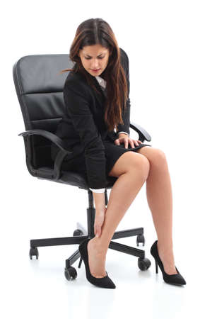 business woman legs: Businesswoman sitting and suffering feet ache isolated on a white background