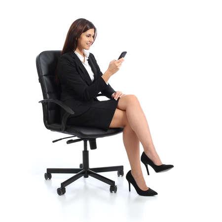 エグゼクティブ ・ ビジネス女性の白い背景に分離された椅子に腰掛けて、スマート フォンを使用して