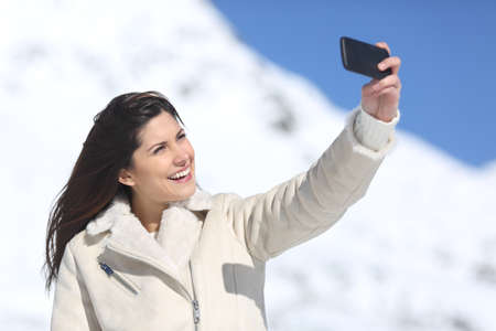 Fashion woman photographing a selfie in winter holidays with a snowy mountain in the background photo