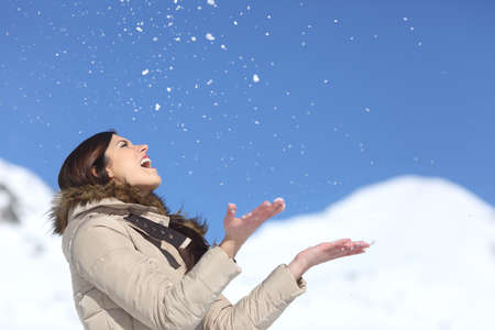 hand free: Happy woman throwing snow in the air on winter holdays with a snowy mountain and a blue sky in the background Stock Photo