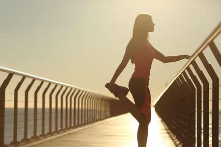 ランナー シルエット ストレッチを行う演習浜辺橋の夕日 写真素材