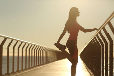 muscular build: Runner silhouette doing stretching exercises at sunset in a bridge on the beach