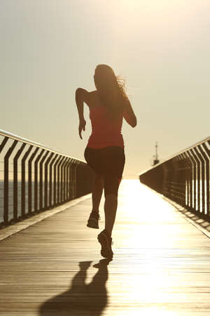 Back view of a runner silhouette running fast at sunset on a bridge on the beach